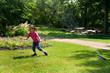 Mädchen rennt unter dem Rasensprenger