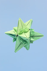 abstract shaped green paper origami isolated on blue