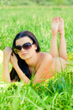 Nude woman lying outdoors with sungasses