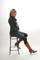 Schwangere Frau in einem engen Kleid, sitzend