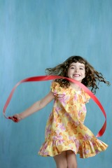 little girl red ribbon tape dancing over green
