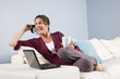 Modern woman relaxed on couch with phone, laptop