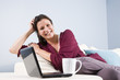 Woman relaxed on couch with laptop and coffee cup