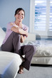 Happy woman sitting on couch smiling
