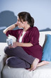 Pensive woman drinking coffee thinking on sofa