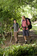 Hispanic father and son hiking on trail in woods