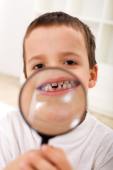 The first lost tooth - boy with magnifier