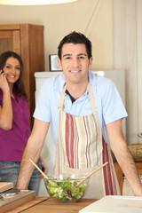 Jeune homme en tablier dans la cuisine