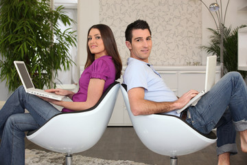 Couple devant ordinateur portable à la maison