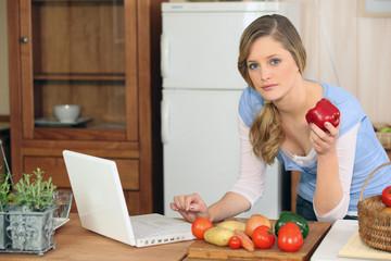 Jeune femme devant un ordinateur portable dans la cuisine