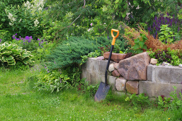 The gardener's spade and a stone wall in the garden