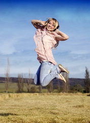 The beautiful young girl jumps in the field
