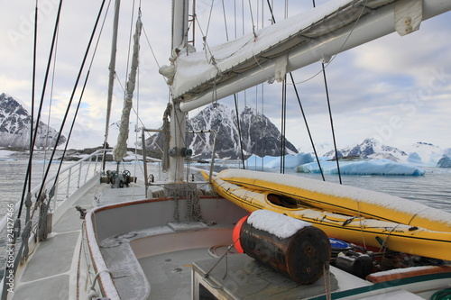 Sailing boat in Antarctic waters with majestic landscape