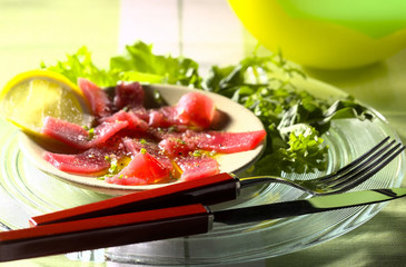 carpaccio of tuna marinated in olive oil with peppers and mixed rocket lettuce