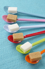 plastic spoons with white and brown sugar lumps