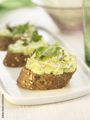cream of avocado with herbs on a bite-size slice of bread