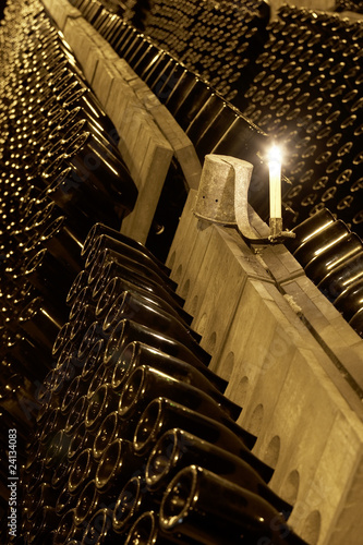 rows of wine bottles on racks in a cellar