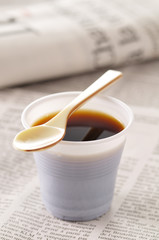 plastic cup of coffee ,spoon and newspaper
