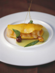rolled mango with grapefruit and hazelnuts with caramel sauce
