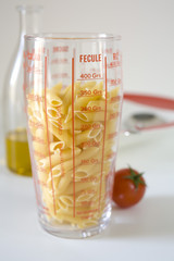 penne in a glass measuring cup