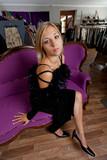 junge Frau sitzt auf einer Couch in einer Boutique poster