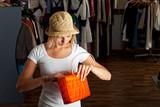 junge Frau durchsucht ihre Handtasche in einer Boutique poster