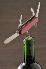 openning a bottle of wine with a corkscrew on a pocket knife
