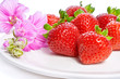 Strawberry on a plate decorated with malva flowers