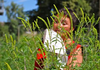 Frau mit Taschentuch hinter Ambrosiapflanzen nießend