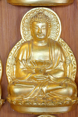 A gold buddha doll on the hard wood.