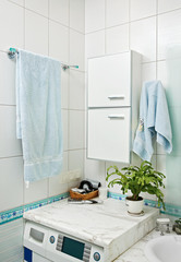 Part of small modern bathroom interior with washing machine