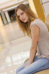 young woman sitting on the bench in the shopping centre