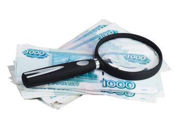 Russian money roubles and magnifying glass