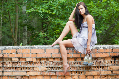 girl sitting on old wall