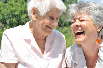 Two elderly women laugh, outdoors