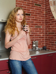 The beautiful girl on kitchen with a coffee mug in hands