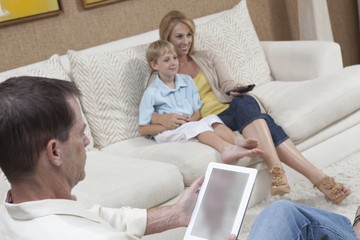 Mother and son watch television while man reads a digital book