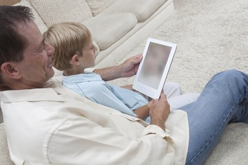 Father and son read a digital book