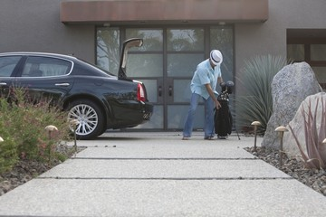 Man lifting golf bag into boot of luxury vehicle
