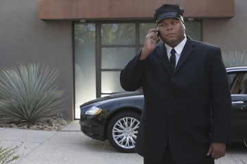 Chauffeur stands on mobile phone withluxury vehicle