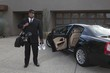 Chauffeur stands with golf equipment near luxury vehicle