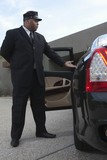 Chauffeur extends hand to client in  luxury vehicle