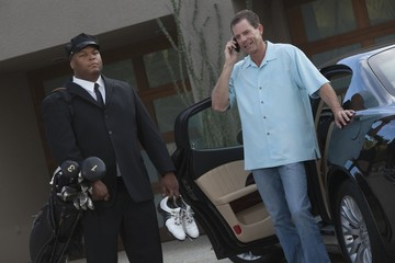 Chauffeur stands with golf equipment and owner of luxury vehicle