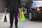Chauffeur holds shopping bags in driveway near luxury vehicle