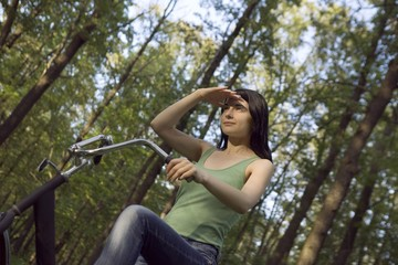Young woman stands shielding eys with bicycle in woodland
