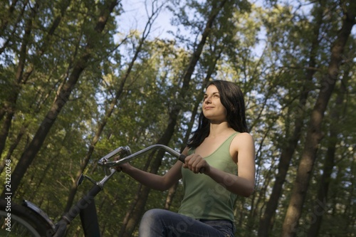 Young woman stands with bicycle in woodland