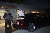 Chauffeur loads suitcases into luxury car at night