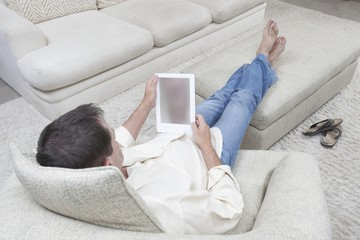 Man sits with feet up reading a digital book
