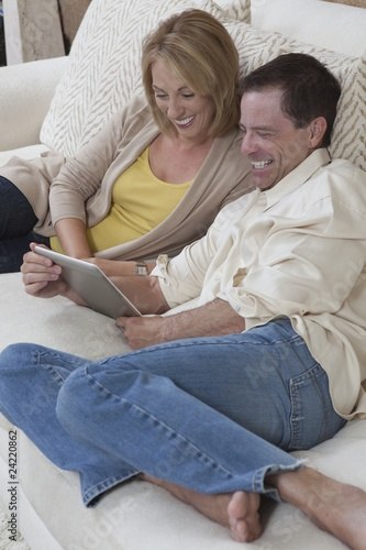 Couple sit reading a digital book