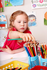 Child drawing pencil in play room.